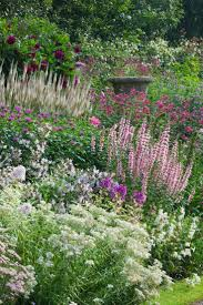 This seemed to me to be cottage garden planting density. Delicate blooms in  pink, white, and purple nearly cover the antique urn in this English garden  at ...