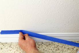 when painting base trim use painter s tape to mask the wall