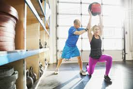 gym instructor gym instructor assisting woman with medicine ball lunge stock