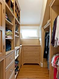 small walk in closet with window over dresser feat floor to ceiling wall shelves and drawers