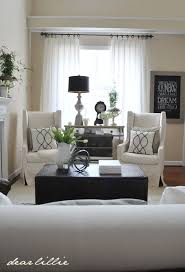 Family room idea: like the double chairs with the pretty dresser and lamp  behind