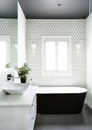small white hex tiles with black grout accentuate the bathtub zone
