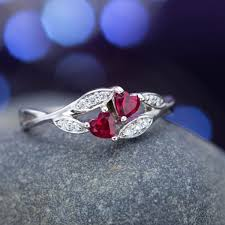 two stone setting with heart cut rubies and bypass style diamond accented shank