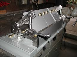 the traditional solution for bending sheet metal in s has been a box and pan brake or finger brake there are plans readily available to make nice ones