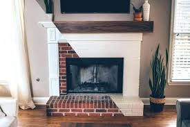 white brick fireplace with reclaimed wood mantel