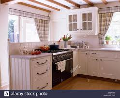white cottage kitchens. Black Range Oven In White Cottage Kitchen With Gray Checked Curtains On The Windows - Stock Kitchens