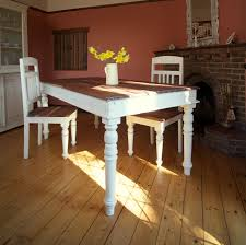 rustic old long trestle dining table painted with white chalk paint color made from reclaimed wood with chairs on hardwood floor tiles ideas