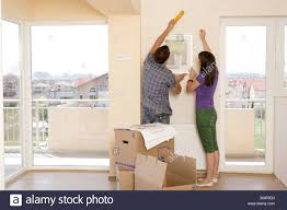 decorating a new apartment. Man And Woman Just Moving In Decorating A New Apartment