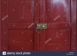 old lock locked with its chain seen from inside an old door painted red