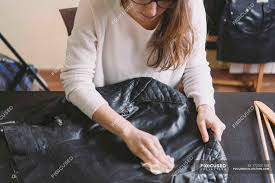 woman cleaning leather jacket stock photos