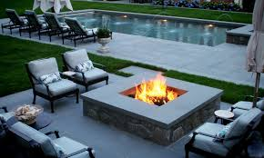 rectangular outdoor gas fireplace around black steel furniture chairs white cushions above granite floor beside swimming pool with relax chairs modern