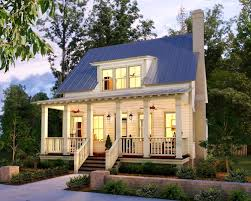 Sweet Little Cottage.love the triple window dormer and tin roof.