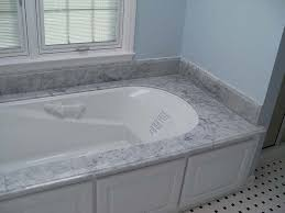 italian white marble tub deck over white cabinets contrasted by light blue bathroom walls