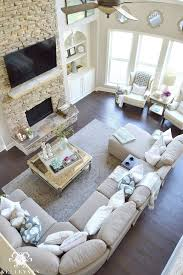 two story living room with stacked stone fireplace and living room layout with fireplace and bay