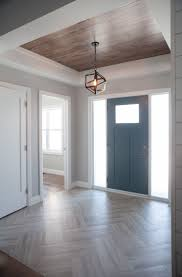 Frosted side lights and a frosted window bring a modern flair to the  craftsman style door, A tray ceiling adds warmth to the bright space ...