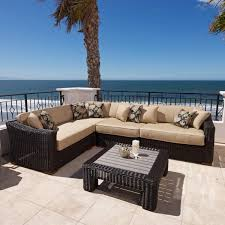 Luxurious patio sectional features broad wooden feat holding a wicker body with light brown thick padded