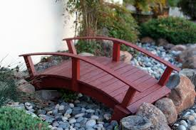 small red wooden bridge over garden with pebbles reaching pond part