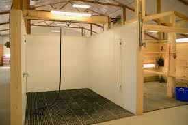a concrete floor and drain covered with rubber mats provides a good surface and footing for the wash stall