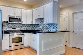 white maple shaker kitchen cabinetry with black granite countertops