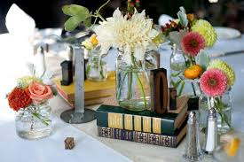 Interesting DIY centerpiece with glass jars, books and fresh flowers