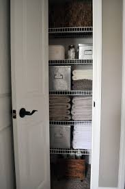 i love the rolling storage cart and big galvanized bins in this small organized linen closet via little glass jar the storage items keep the messier