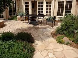 exterior patio flooring options with oval table black iron dining chairs near green plants
