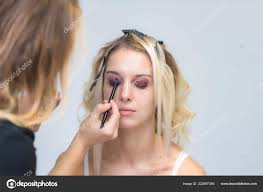 work professional makeup artist beautician makes makeup brush face beautiful stock photo