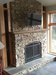 fireplace surround using natural veneer stone with a cut bluestone hearth and chestnut barn beam mantle