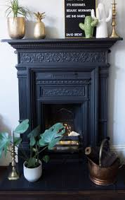 my cast iron fireplace surround with ceramic cactus vases brass pineapple and a letter board