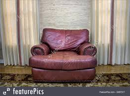 house living comfortable leather couch sitting in a room between two windows