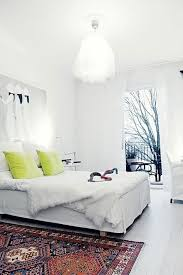 all white bedroom with a brightly colored scandinavian rug