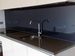 a close up of black glass splashbacks installed behind a sink