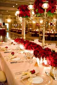 Candelabra and red rose centrepiece, red and gold table settings and  decorations. I love the red flowers against the white table cloths.