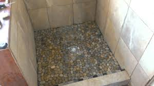 impressive random sized river grey pebble shower floor with marble wall tiled as small space country shower room designs