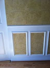use chair rail molding and picture frames with wallpaper on top and inside picture frames to
