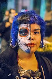 woman with half face sugar skull makeup blue hair gouged ears dia de