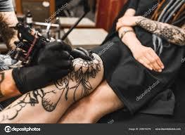 девушка с дреды в тату салон мастер создает рисунок на теле молодой