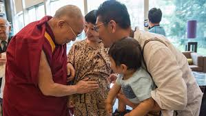 compassion and the individual the th dalai lama his holiness the dalai lama blessing an expectant mother as he leaves his hotel in narita