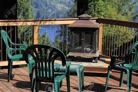 four plastic chairs on a scenic sunny outdoor deck with a fireplace on a raised platform