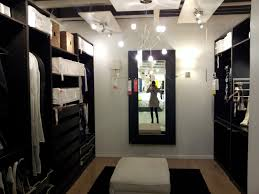 galley black stained wooden walk in closet for bedroom with chandelier and ceiling lights also black