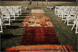 the alter was a 16 foot tee with cascading wild flowers and tered disco along the lawn navajo and persian rugs lined the aisle