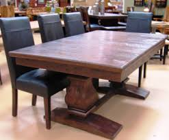large antique expandable dining table with black leather chairs dining room