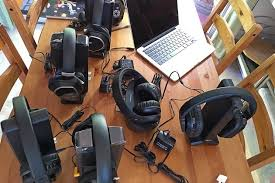 home theater headphones. a collection of black headphones on wooden table. also pictured with an open laptop home theater l