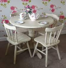 idyllic round dining table features shabby white set and