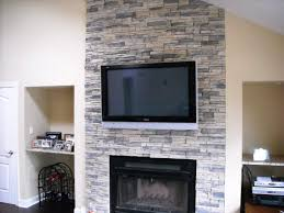 interior paint color and stacked stone veneer for stone veneer fireplace and shelves with wine racks plus tv over fireplace and hardwood flooring with