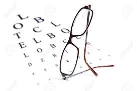 Reading Glasses Balanced On An Opthalmology Vision Testing Chart
