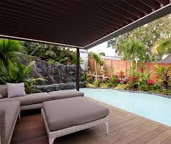 pool deck with pergola covering outdoor lounge furniture