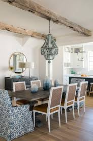 a round mirror hangs above a black console table in a dining room featuring a black trestle dining table illuminated by a blue beaded chandelier hung from a