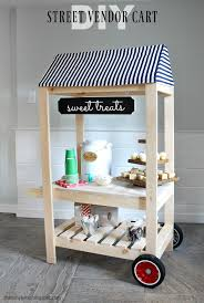 a diy tutorial to build a kids size street vendor cart perfect for pretend play free plans include service area with storage shelf awning and push handle