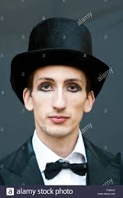 a man with heavy eye makeup dressed as a ringmaster in a top hat and bow tie